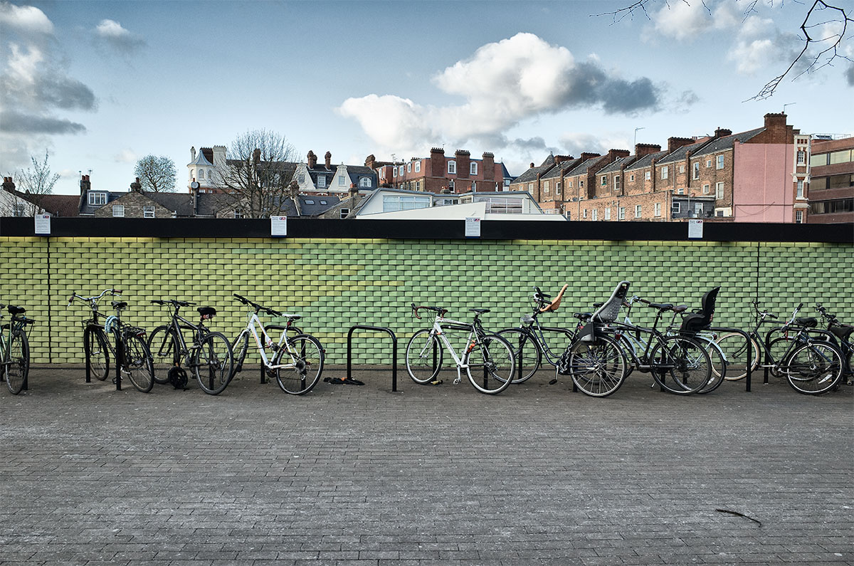 Bikes against green wall with view of houses over wall