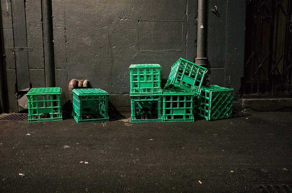 Green bottle crates in alley