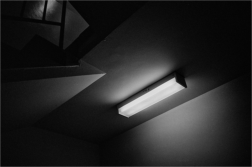 Fluorescent light on stairway. Black and white image.
