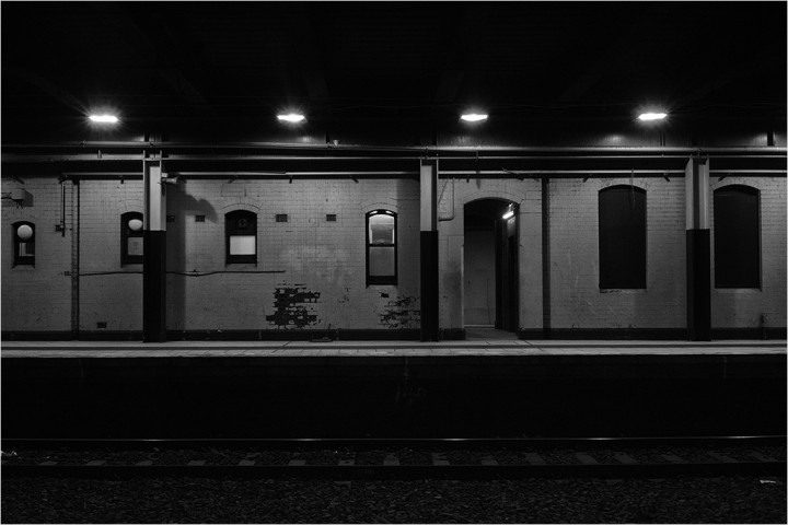 View across railway platform. Bright lights.